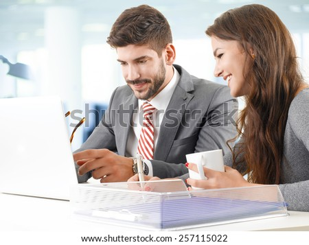 Portrait of sales team working on laptop at presentation while sitting at desk in office.  - stock photo