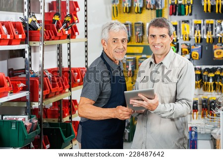Portrait of salesman and customer using tablet computer in hardware store - stock photo