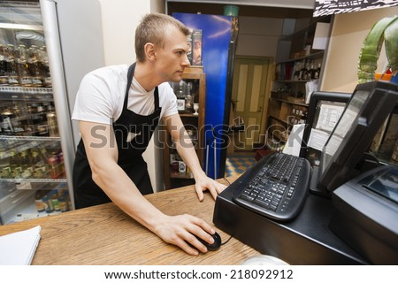 Portrait of salesman using computer at cash counter in supermarket - stock photo