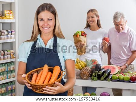 Portrait of saleswoman holding carrot basket while father and daughter shopping at supermarket - stock photo