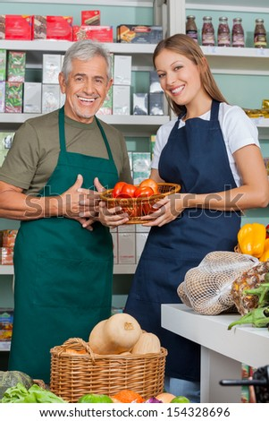Portrait of saleswoman holding vegetable basket standing with male colleague in supermarket - stock photo