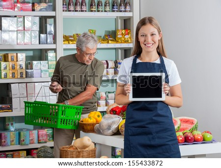 Portrait of saleswoman showing digital tablet while senior man shopping in background - stock photo
