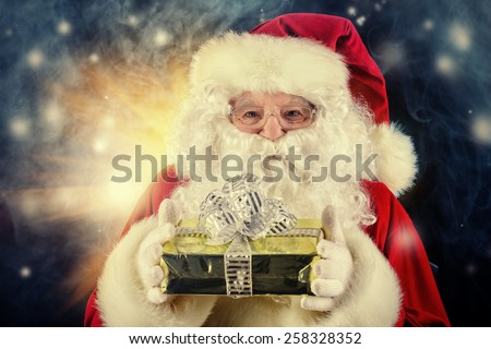 Portrait of Santa Claus holding gift box. Christmas time.  - stock photo