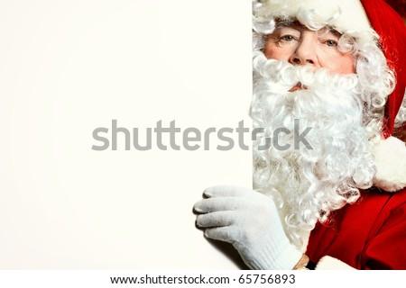 Portrait of Santa Claus holding white board. Christmas. - stock photo