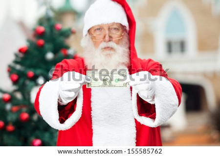 Portrait of Santa Claus showing one dollar note against Christmas tree - stock photo