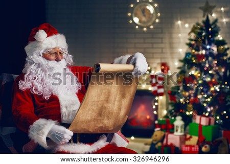 Portrait of Santa Claus sitting at his room at home near Christmas tree - stock photo