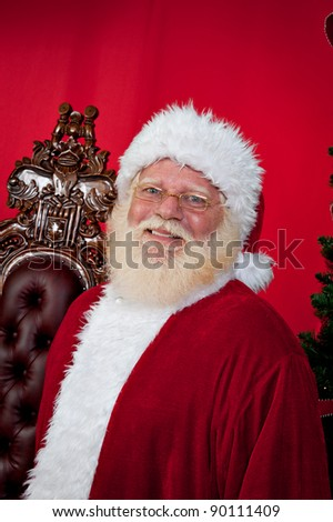 Portrait of Santa Claus standing in front of his chair at Christmas time.