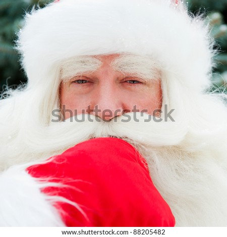Portrait of Santa Claus standing with hand on chin outdoors at christmas tree. Snow falls. Natural light - stock photo