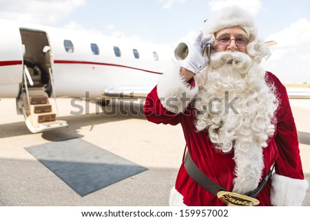 Portrait of Santa Claus using mobile phone against private jet at airport terminal - stock photo
