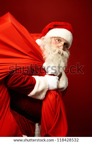 Portrait of Santa Claus with huge red sack looking at camera