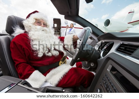 Portrait of Santa driving convertible with pilot and airhostess standing in background at airport terminal - stock photo