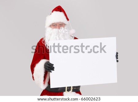 Portrait of Santa holding blank white board, looking at camera, isolated on gray background.? - stock photo