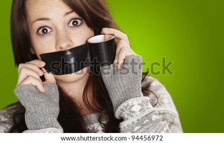 portrait of scared girl being silenced by herself over green background - stock photo
