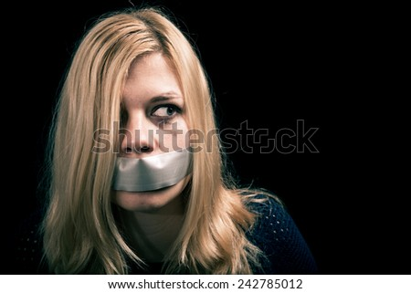 Portrait of scared kidnapped woman hostage with tape over her mouth - stock photo