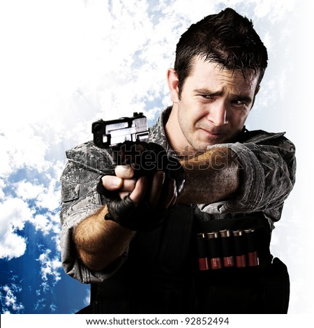 portrait of scared soldier aiming with gun against a cloudy sky background - stock photo