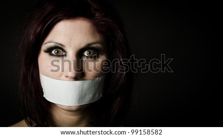 Portrait of scared woman with tape over her mouth - stock photo