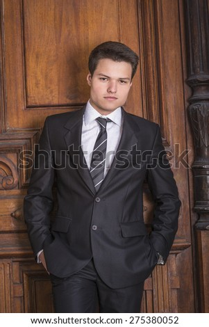 Portrait of School Boy. Dressing formally in black suit, necktie, white shirt, hands in pockets, a young handsome college student standing against vintage style office door on campus, looking at you. - stock photo