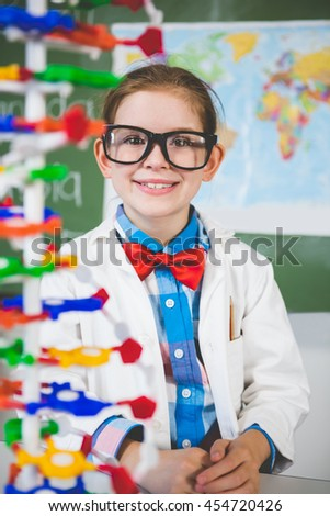 Portrait of school girl assembling molecule model for science project in lab at school - stock photo