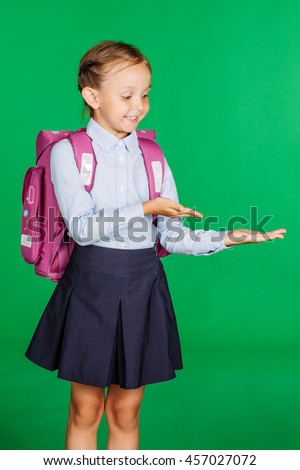 portrait of school girl in a school uniform showing open hand palm with copy space for product or text. Learning, idea and school concept. Image on green background. - stock photo