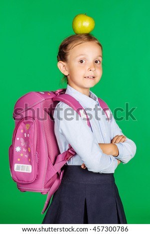 portrait of school girl in a school uniform with apple. Learning, idea and school concept. Image on green background. - stock photo