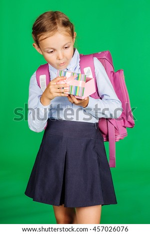 portrait of school girl in a school uniform with gift box. Learning, idea and school concept. Image on green background. - stock photo
