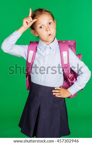 portrait of school girl in a school uniform with idea gesture. Learning, idea and school concept. Image on green background. - stock photo