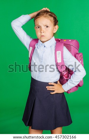 portrait of school girl in a school uniform with scratching hrad. Learning, idea and school concept. Image on green background. - stock photo