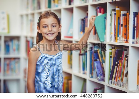 Portrait of school girl taking a book from bookshelf in library at school