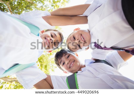 Portrait of school kids forming huddle in campus at school - stock photo