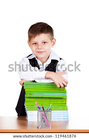 Portrait of schoolboy with books standing at a desk in the classroom - stock photo