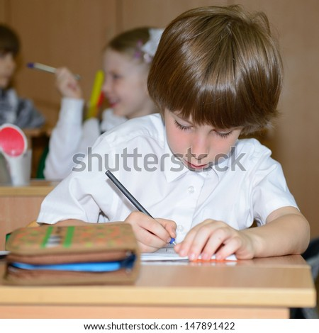 Portrait of schoolboy writing at workplace with another children in classroom on background - stock photo