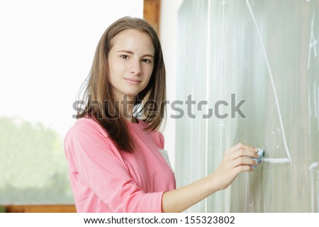 Portrait of schoolchild at the blackboard looking at camera - stock photo