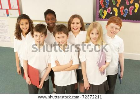 Portrait Of Schoolchildren Standing In Classroom - stock photo