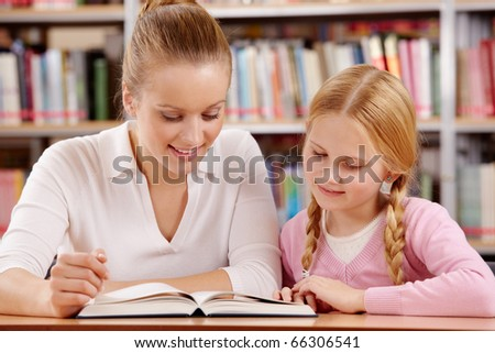 Portrait of schoolgirl and teacher reading interesting book in library