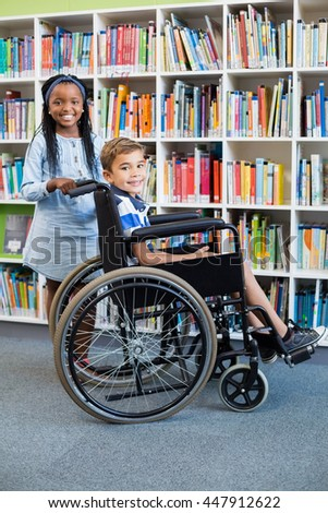 Portrait of schoolgirl standing with schoolboy on wheelchair in library