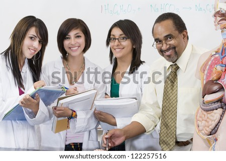 Portrait of science professor with female students - stock photo