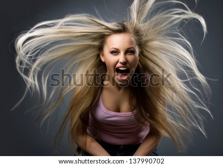 portrait of screaming young woman with long blond flying hair on dark-grey background