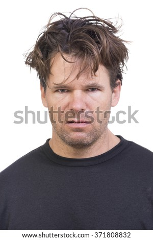 Portrait of scruffy Caucasian man with long messy hair and expression of disgust on white background - stock photo