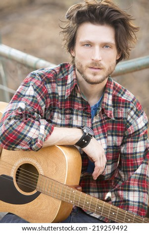 Portrait of scruffy man with a guitar - stock photo