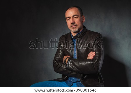 portrait of seated mature man in leather jacket posing looking at the camera with hands crossed in gray studio background