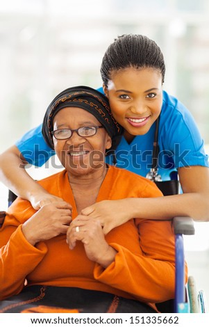portrait of senior african disabled woman and her caregiver - stock photo