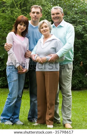 Portrait of senior and young couples in casual clothes outdoors - stock photo