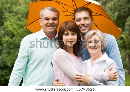 Portrait of senior and young couples under umbrella outdoors - stock photo