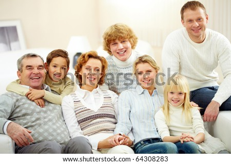 Portrait of senior and young couples with their children looking at camera at home - stock photo