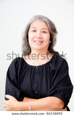 portrait of senior asian woman smiling with arms fold - stock photo