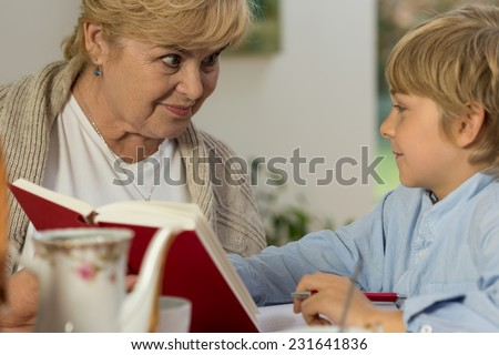 Portrait of senior babysitter caring about schoolboy - stock photo