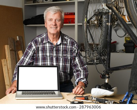 Portrait of senior bike shop owner sitting at desk behind the laptop with white screen. Active old man looking at camera and smiling. Small business.  - stock photo