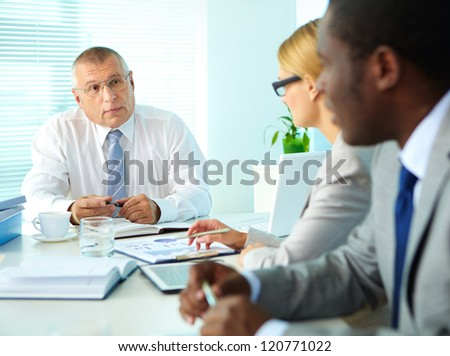 Portrait of senior boss looking at his employees at meeting - stock photo