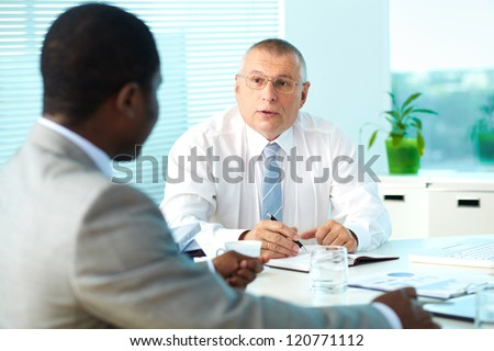 Portrait of senior boss talking and his employee at meeting - stock photo