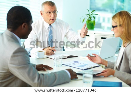 Portrait of senior boss talking and his employees at meeting - stock photo